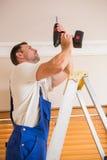 使用一个无绳的钻子的杂物工对天花板 库存图片