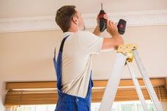 使用一个无绳的钻子的杂物工对天花板 库存照片