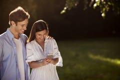 使用一个智能手机的夫妇在公园 库存照片