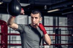 使用一个沙袋的男性拳击手在健身房 免版税库存照片