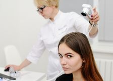 使用一个特别设备,皮肤病学家审查一根耐心妇女头发 库存图片