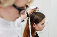 使用一个特别设备,皮肤病学家审查一根耐心妇女头发 库存照片