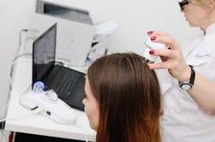 使用一个特别设备,皮肤病学家审查一根耐心妇女头发 免版税库存图片