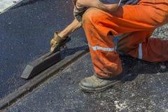 使用一个特定工具的工作者涂石油沥青砂胶 免版税库存照片