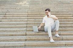 使用一个膝上型计算机和电话的快乐的年轻商人在台阶 免版税库存照片