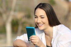 使用一个蓝色巧妙的电话的妇女户外 图库摄影