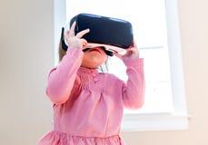 使用一个虚拟现实耳机的小孩女孩 免版税库存图片