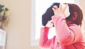使用一个虚拟现实耳机的小孩女孩 免版税库存照片