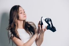 使用一个虚拟现实耳机的愉快的少妇 看在手上的现实玻璃 库存照片