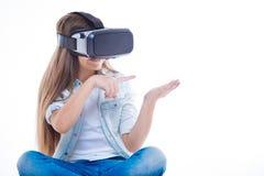 使用一个虚拟设备的高兴逗人喜爱的女孩 库存照片