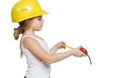 使用一个评定的磁带的小女孩建造者 免版税库存照片