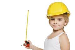 使用一个评定的磁带的小女孩建造者 库存图片