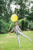 使用一个黄色气球 走在欧洲庭院里的愉快的美丽的年轻studient女孩 她查看照相机 库存照片