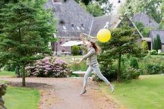使用一个黄色气球 走在欧洲庭院里的愉快的美丽的年轻studient女孩 她查看照相机 免版税库存照片