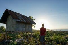 使用一件红色衬衣的年轻人从在Pemana海岛弗洛勒斯印度尼西亚上的小山的顶端享受日出 免版税库存图片