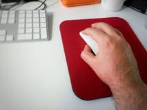 使用一只白色计算机老鼠的男性手 库存图片