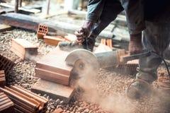 使用一台专业角度研磨机的建筑工人为切开砖和修筑内墙 库存图片