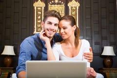 使用一台便携式计算机的年轻夫妇在一个亚洲旅馆客房 免版税图库摄影