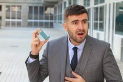 使用一台吸入器的气喘商人在工作 免版税库存照片