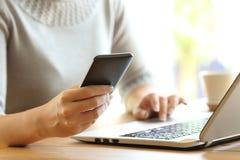 使用一台手机和膝上型计算机的妇女手在书桌上 免版税库存照片