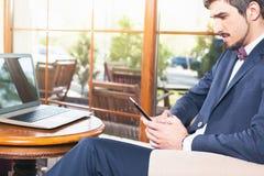 使用一台手机和膝上型计算机的英俊的人在咖啡馆 库存照片