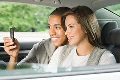 使用一台手机的年轻夫妇在汽车 免版税库存图片