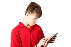 使用一台数字式片剂个人计算机的十几岁的男孩 库存照片