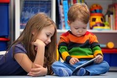 使用一台数字式片剂计算机的女孩和兄弟乐趣 免版税库存图片