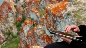 使用一台片剂个人计算机的女孩的手在岩石,奥尔洪岛,贝加尔湖 影视素材