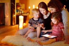使用一台片剂个人计算机的愉快的家庭由壁炉 库存图片