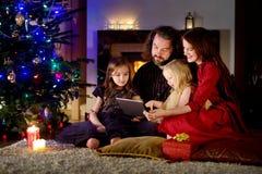 使用一台片剂个人计算机的愉快的年轻家庭在家由一个壁炉在温暖和舒适客厅 库存照片