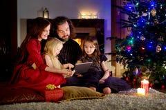 使用一台片剂个人计算机的愉快的年轻家庭在家由一个壁炉在温暖和舒适客厅 图库摄影