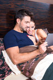 使用一台片剂个人计算机的美好的年轻夫妇在床上 库存照片