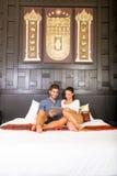 使用一台片剂个人计算机的年轻夫妇在一个亚洲旅馆客房 库存图片