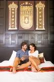 使用一台片剂个人计算机的年轻夫妇在一个亚洲旅馆客房 免版税图库摄影