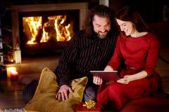 使用一台片剂个人计算机的年轻愉快的夫妇由一个壁炉在一个舒适黑暗的客厅 免版税图库摄影
