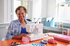 使用一台缝纫机的资深黑人妇女看对照相机 库存图片