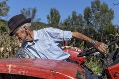 使用一台老拖拉机的资深农夫犁他的土地 图库摄影