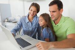 使用一台膝上型计算机个人计算机的家庭在厨房里 库存图片