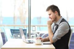 使用一台膝上型计算机的商人在咖啡店 库存图片