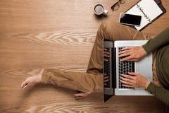 使用一台膝上型计算机的商人手有一杯咖啡的和聪明 免版税库存图片
