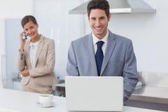 使用一台膝上型计算机的商人早晨 库存图片