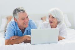 使用一台膝上型计算机的夫妇在床上 库存图片