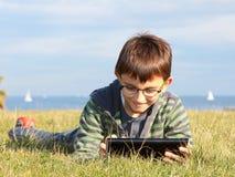 使用一台膝上型计算机的孩子在草 库存图片