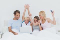 使用一台膝上型计算机的家庭在床上 免版税库存照片