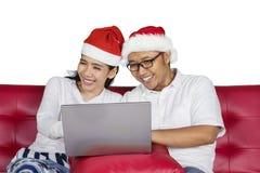 使用一台膝上型计算机的年轻夫妇在演播室 库存照片