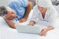 使用一台膝上型计算机的快乐的夫妇在床上 库存图片