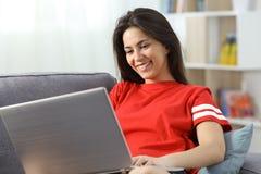 使用一台膝上型计算机的愉快的十几岁的女孩在长沙发在家 免版税库存图片