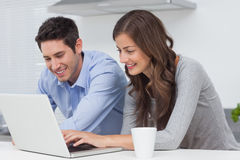 使用一台膝上型计算机的愉快的夫妇在厨房里 库存图片