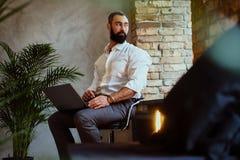 使用一台膝上型计算机的都市有胡子的男性在屋子里 免版税库存照片